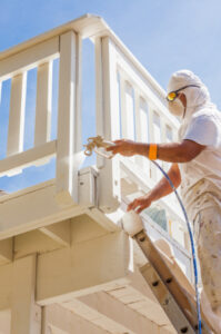 A skilled painter painting the deck of a house in Windsor, ON