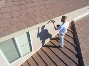 A contractor painting the exterior of a house in Windsor, ON