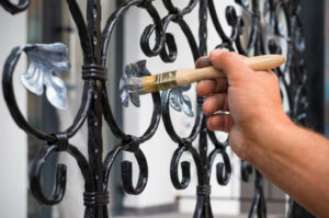 An awesome contractor finishing painting a fence in a residential area in Windsor, ON